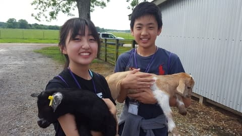 Students holding goats